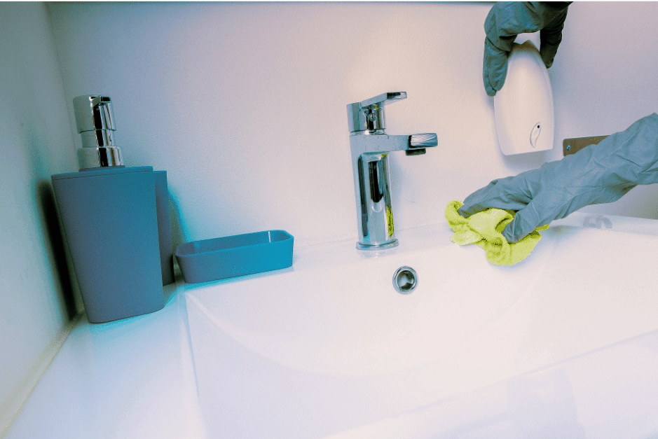Cleaner with gloves on and cloth cleaning a bathroom sink