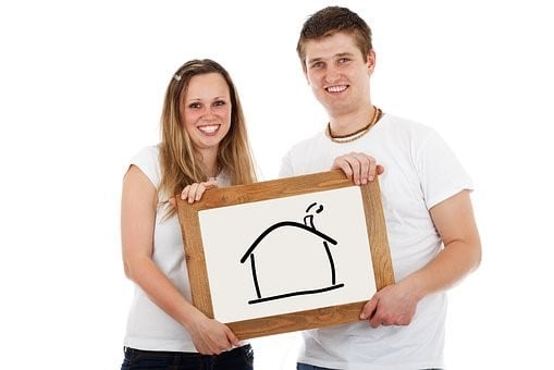 Couple holding a picture of a house