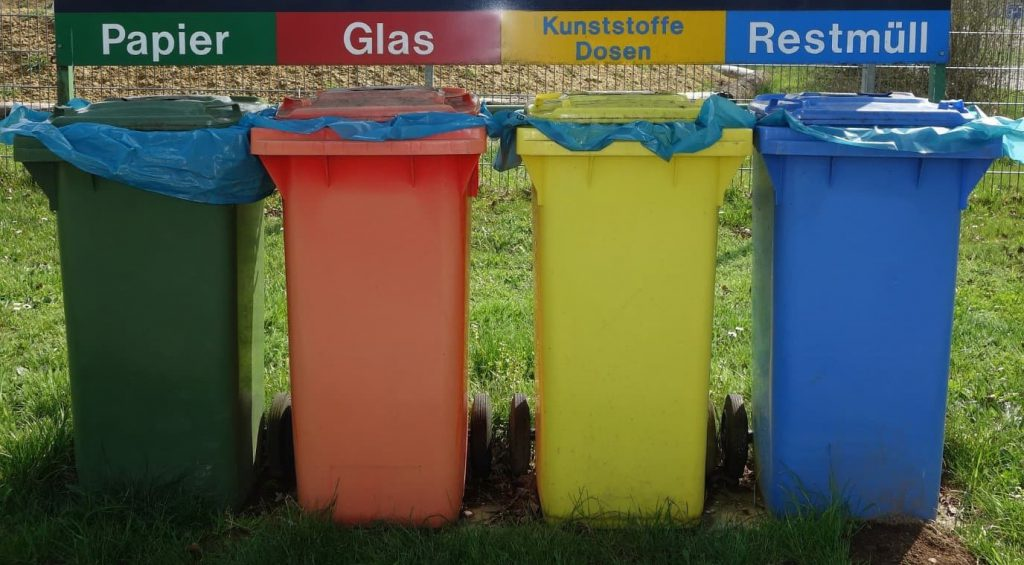 Different coloured bins, for paper, glass, recycling & general waste