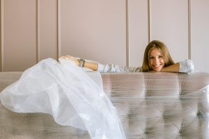 woman holding bubble wrap over a packaged sofa