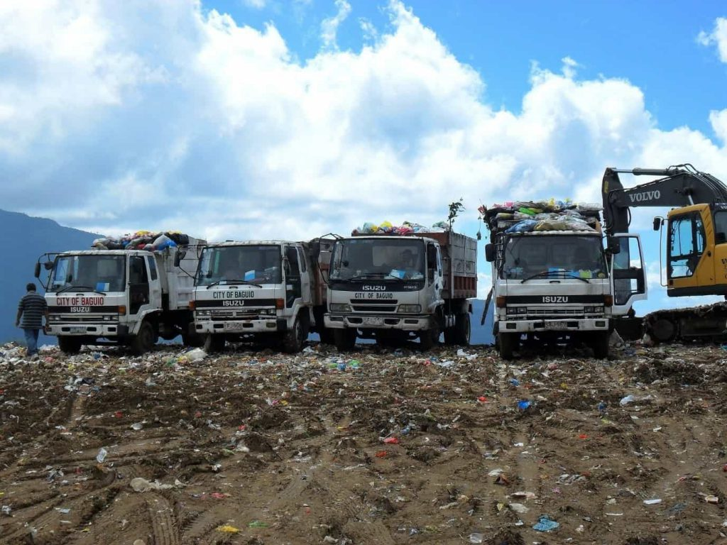 Rubbish trucks, digger on landfill site