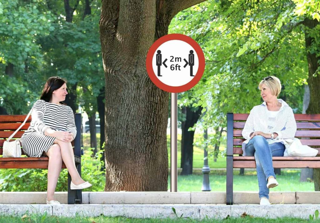 Two women sitting in park, separate benches, social distancing